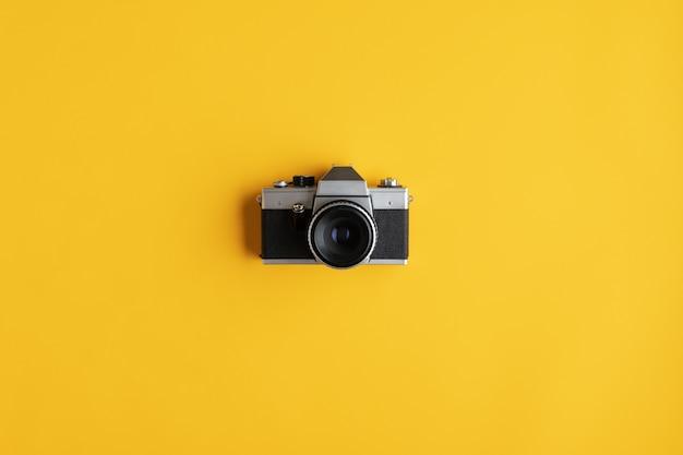 Rustieke oude analoge camera die over geel oppervlak wordt geplaatst