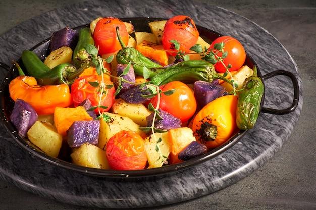 Rustieke, ovengebakken groenten in ovenschaal. seizoensgebonden vegetarische veganistische maaltijd op donker stenen bord