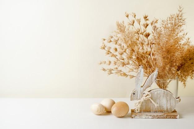 Rustieke paasdecoratie met houten konijn, eieren en pampagras, exemplaarruimte