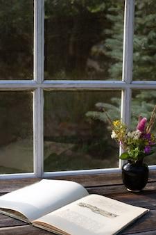 Rustieke retro sfeer met oud boek en boeket van wilde bloemen op houten tafel op het terras. verticaal formaat, kopieer ruimte