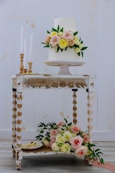 Rustieke stijl bruidstaart met verse bloemen en kaarsen op vintage tafel.