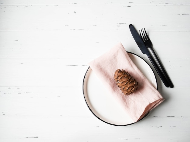 Rustieke tafel instelling met plaat, roze servet, eucalyptus en apparaten op witte houten tafel. bovenaanzicht