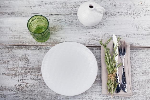 Rustieke tafel setting met rozemarijn op licht houten tafel met copyspace. vakantiedecoratie in provençaalse stijl. romantisch diner. bovenaanzicht