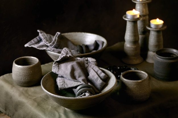 Rustieke tafelsetting met leeg ambachtelijk keramisch servies, grijze ruwe kommen en kopjes, brandende kaarsen op linnen tafelkleed. donkere achtergrond