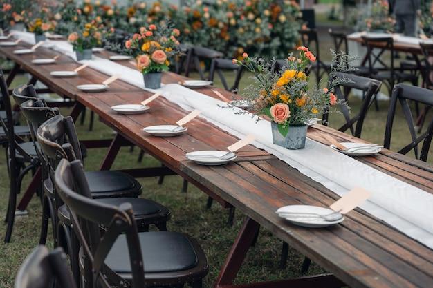 Rustieke trouwstijl, houten eettafel met bloemendecoratie en servies