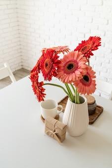 Rustieke witte bakstenen muur met rode verse gerbera's in een witte vaas