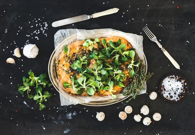 Rustieke zelfgemaakte pizza met verse veldsla, champignons en knoflook over donkere grunge