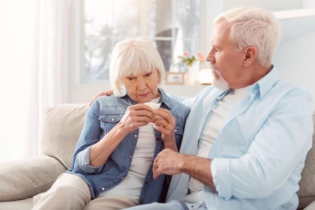 Rustig aan. liefdevolle senior man zittend op de bank naast zijn vrouw, haar knuffelen en troosten terwijl ze huilde na het horen van slecht nieuws