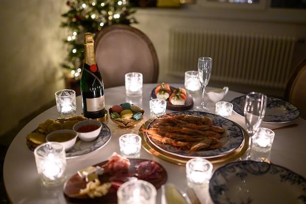 Rustig beeld van interieur moderne huis woonkamer versierd kerstboom en geschenken, sofa, tafel bedekt met deken