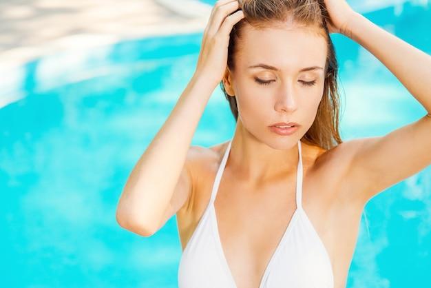 Rustig en ontspannen voelen. close-up van prachtige jonge vrouw in witte bikini die bij het zwembad staat en de ogen gesloten houdt