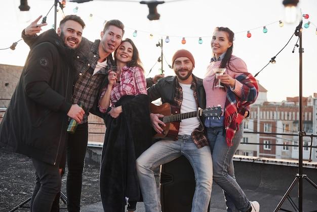 Rustig en opgewekt. feest op het dak. vijf knappe vrienden die poseren voor de foto met alcohol en gitaar