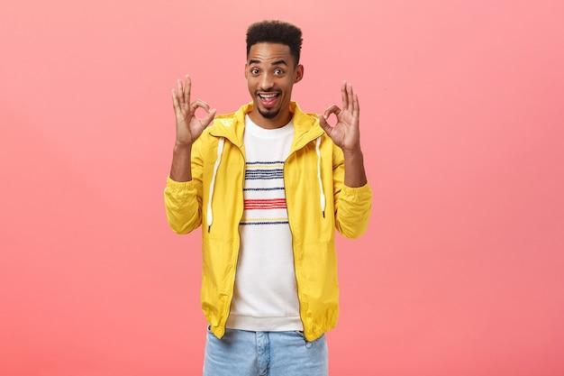 Rustig jongens, ik heb het. portret van een gelukkige, stijlvolle en coole afro-amerikaan met een afro-kapsel in een trendy gele jas die een goed of goed gebaar opheft en een uitstekend idee hoort over roze achtergrond