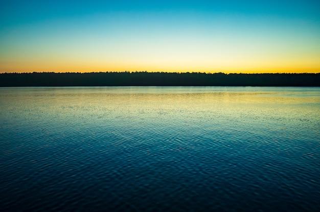 Rustig minimalistisch landschap met kalm water en heldere luchten eenvoudige natuurlijke achtergrond ruimte kopiëren
