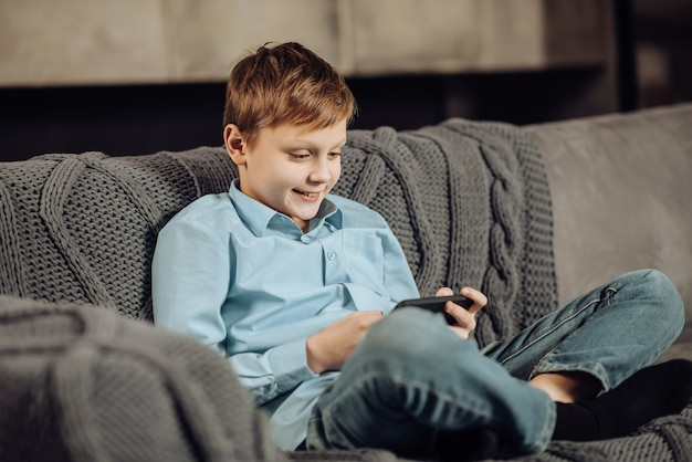 Rustig tijdverdrijf. vrolijke pre-tienerjongen die met gekruiste benen op de bank zit en aan de telefoon speelt terwijl hij aangenaam glimlacht