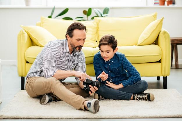 Rustige attente man van middelbare leeftijd zittend op de vloer en toont zijn zoon een moderne camera