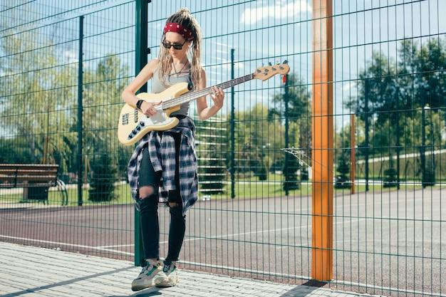 Rustige geconcentreerde getalenteerde muzikant die vrijetijdskleding draagt en gitaar speelt terwijl hij op het sportveld staat
