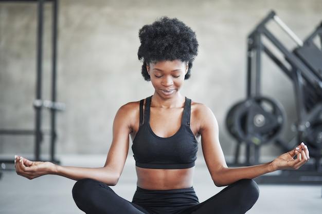 Rustige geest. afro-amerikaanse vrouw met krullend haar en in sportieve kleding hebben fitnessdag in de sportschool