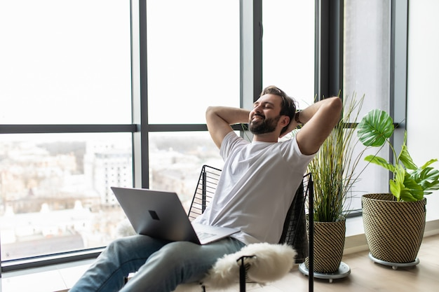Rustige gelukkig gezonde jonge man ontspannen op comfortabele fauteuil met laptop.