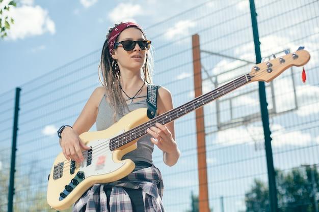 Rustige jonge dame vrijetijdskleding en een donkere zonnebril dragen tijdens het buiten spelen van de gitaar in zonnige dag