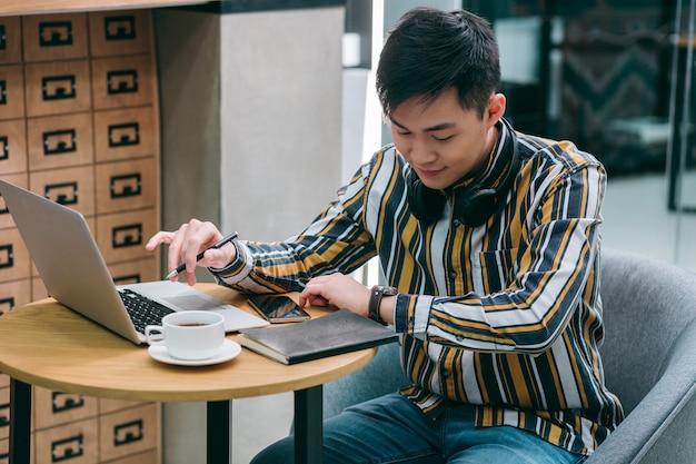 Rustige jonge man die voor een laptop zit en naar het horloge kijkt
