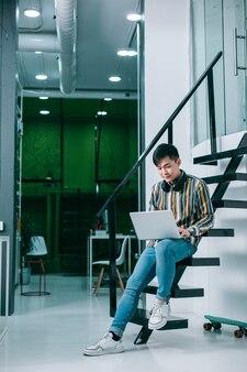 Rustige jonge man in vrijetijdskleding zittend op de trap in een modern kantoor en met behulp van een laptop