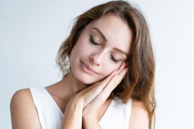 Rustige jonge vrouw die slaapgebaar met haar gesloten ogen maakt