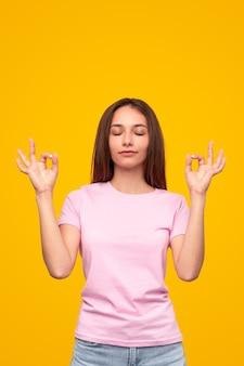 Rustige jonge vrouw in casual outfit met mudra-vingers die meditatie en mindfulness beoefenen