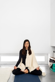 Rustige jonge vrouw in sportkleding en sjaal beoefenen van meditatie in lotus houding in minimalistische stijl kamer thuis