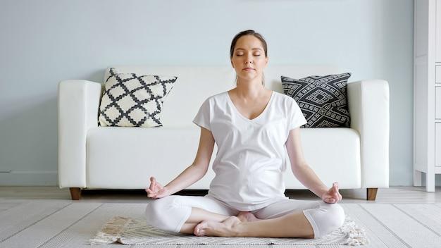 Rustige jonge zwangere vrouw in het wit mediteert zittend in lotushouding op vloerkleed in de buurt van designer sofa in ruime kamer thuis close-up