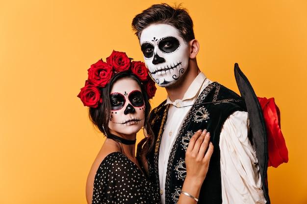 Rustige kerel en donkerharig meisje. vrouw met kroon van rozen omhelst mexicaanse man met geschilderd gezicht.