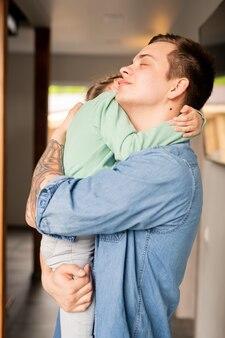 Rustige liefdevolle hipster jonge vader met tatoeage op arm ogen gesloten houden terwijl schattige dochter knuffelen en haar troosten