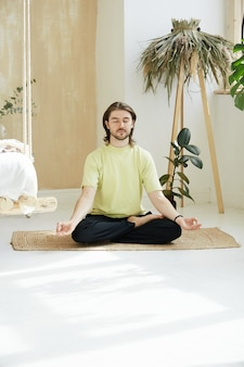 Rustige man in lotus houding en yoga mudra thuis, jonge mindfull man mediteren op de vloer