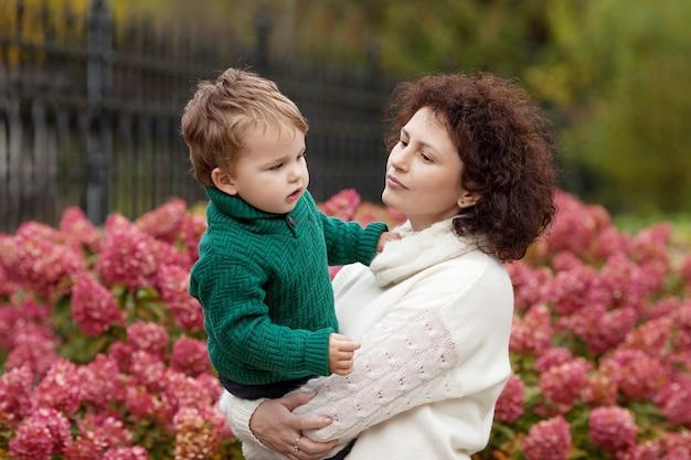 Rustige moeder en haar lieve kleine jongen in een park schattig kind spelen met moeder in het park moeder a