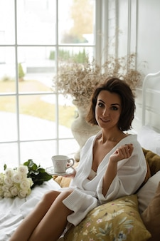 Rustige mooie dame in een badjas met een kopje op een bord terwijl u ontspant bij het raam. bloemen op de