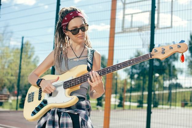 Rustige mooie jonge dame met dreadlocks dragen van een zonnebril tijdens het spelen van de gitaar op het sportveld