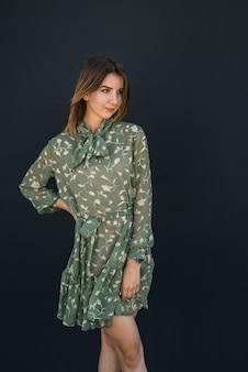 Rustige mooie jonge vrouw in elegante groene jurk in de buurt van zwarte muur. mode vrouwelijk portret