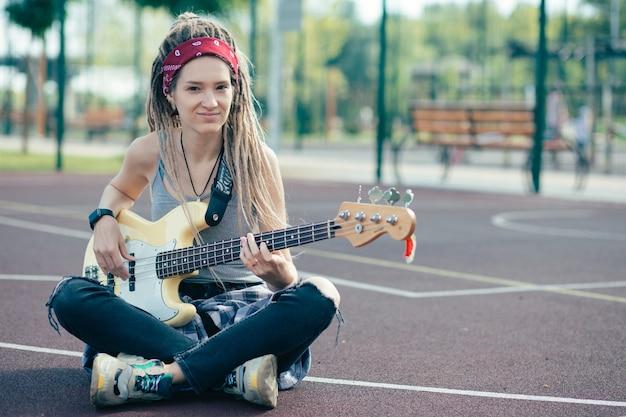 Rustige mooie jonge vrouw met dreadlocks zittend op de grond op het sportveld en naar je te kijken terwijl ze haar gitaar vasthoudt