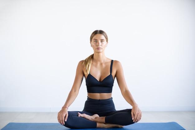Rustige mooie vrouw die yogaoefening doet die op wit wordt geïsoleerd.