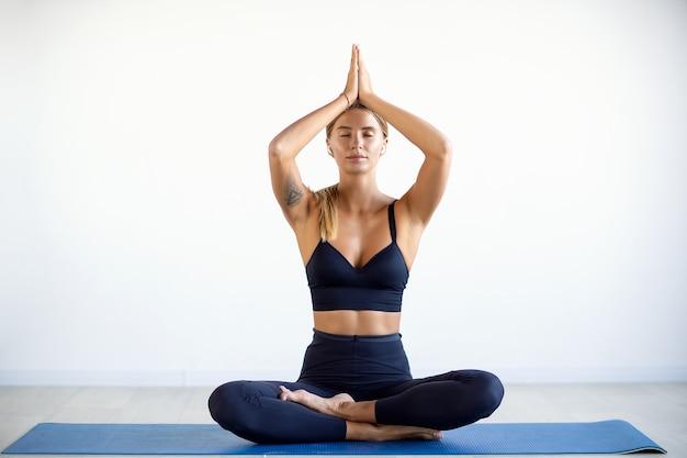 Rustige mooie vrouw die yogaoefening doet