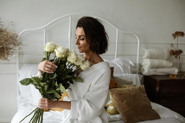 Rustige mooie vrouw in een badjas die witte rozen ruikt zittend op het bed met gesloten ogen.