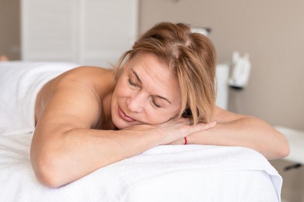 Rustige naakte rijpe vrouw met gesloten ogen liggend onder handdoek op massagetafel in afwachting van therapeut in wellness-studio