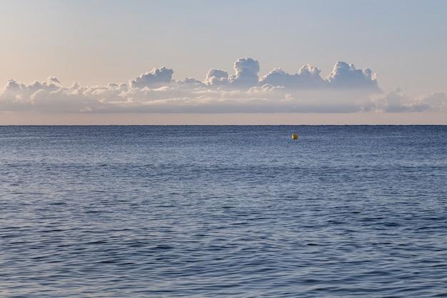 Rustige ochtend op leeg strand met afdrukken van een autoband op zand met zee en wolken aan de oppervlakte