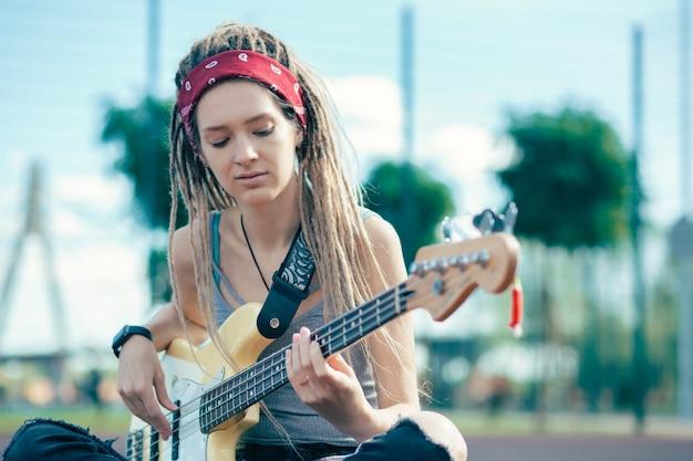 Rustige ontspannen jonge vrouw met dreadlocks bedachtzaam gitaar spelen terwijl zittend op de grond
