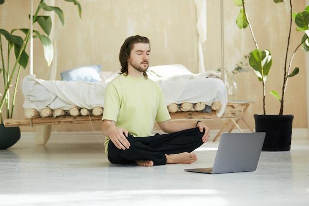 Rustige ontspannen man in lotus houding met laptop op de vloer, knappe man in groen shirt zitten in meditatie en concentreren