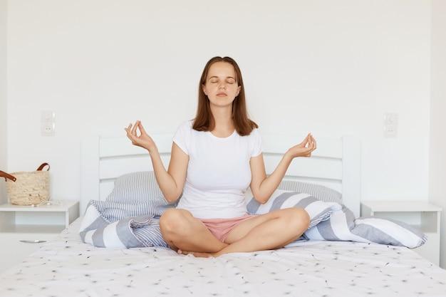 Rustige ontspannen vrouw met donker haar met een wit casual t-shirt en korte broek, zittend op bed in lichte slaapkamer in lotushouding, yogabeoefening en mediteren.
