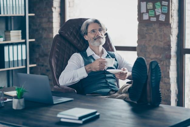 Rustige oude bedrijfsmens die in bureau met koffiekop rust
