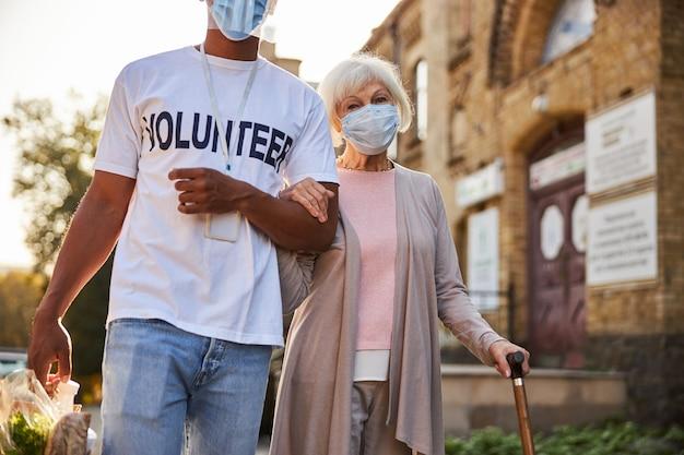 Rustige oudere dame die een medisch masker draagt met een wandelstok terwijl een verantwoordelijke vrijwilliger aankopen in een papieren zak draagt