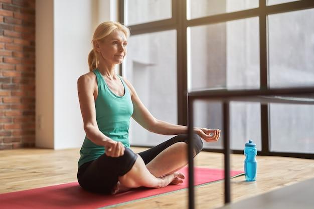 Rustige rijpe blonde vrouw die overdag yoga beoefent en thuis op de vloer mediteert