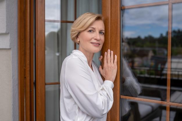Rustige rijpe mooie vrouw die in de deuropening staat