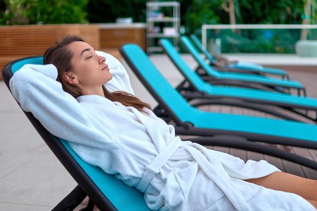 Rustige, serene vrouw die een badjas draagt met gesloten ogen en handen achter het hoofd, ontspannen en liggend op een ligstoel in het wellness-kuuroord. tevredenheid, een goed gevoel en recreatietijd. gemakkelijke levensstijl